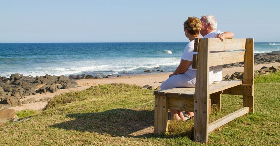 Elderly couple sitting on bench watching the ocean